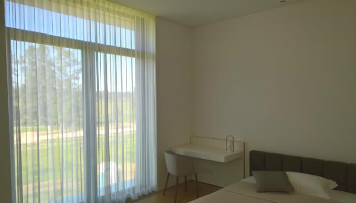 Mežaparka rezidences - Villa Corylus ar gaisīgiem dienas aizkariem, kas papildina rūpīgi veidoto interjera dizainu.